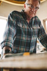 Senior carpenter with protective eye wear