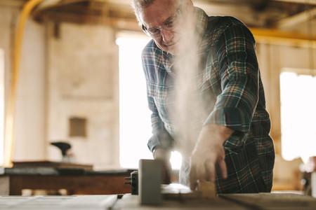 Senior carpenter cutting wood on table saw machine