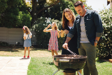 Couple cooking grilled food in backyard with children playing
