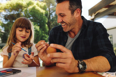 Smiling man sitting with his daughter painting easter eggs
