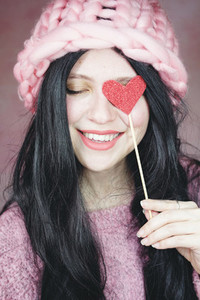 Romantic woman wearing pink clothes and holding a red heart