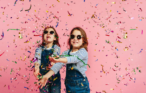Girl twins playing with confetti