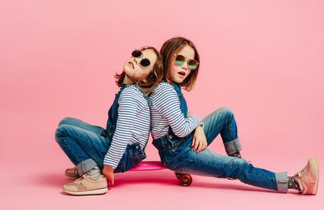 Stylish cute girls in fashion clothes on a skateboard