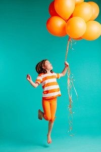 Happy girl jumping with orange balloons