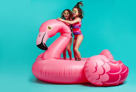 Smiling girls having fun on inflatable toy flamingo