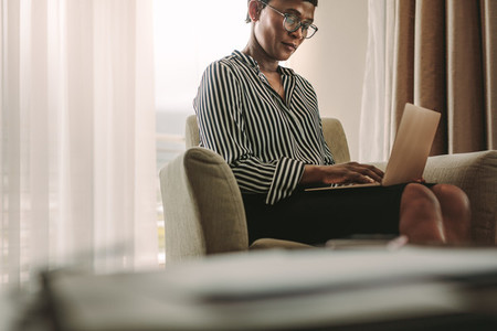 Businesswoman on business trip working from hotel room