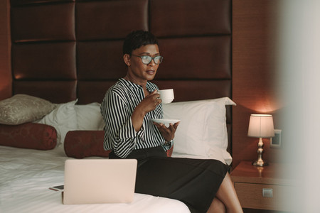 Businesswoman relaxing in hotel room having coffee