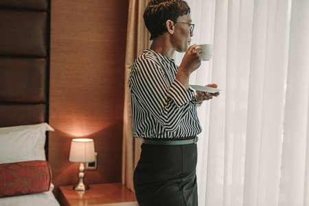 Businesswoman standing in hotel room with a cup of coffee