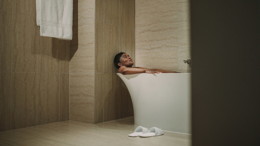 Female relaxing in bathtub with her eyes closed