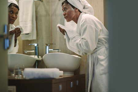 African female cleaning her face with towel in bathroom