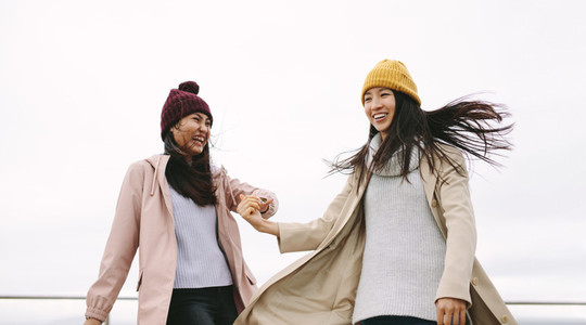 Cheerful girl friends in winter clothes standing together outdoo