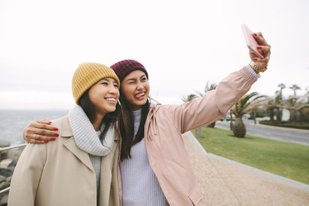 Happy girl friends taking a selfie standing outdoors