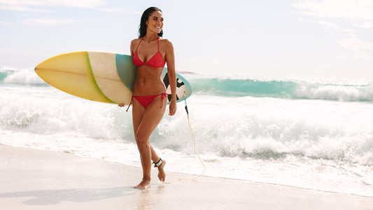 Smiling woman walking out of sea with surfboard