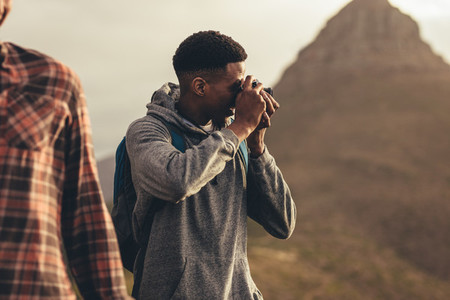 Man taking pictures during a hike with friends