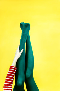 Pop art piece of young woman legs in tights against a yellow bac