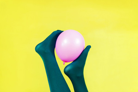 Green legs of a woman holding a pink balloon against a yellow wa