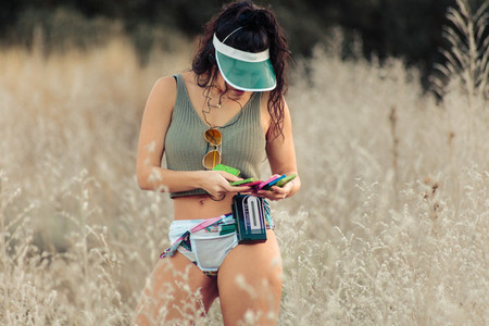 Young brunette woman selecting old cassettes in the field
