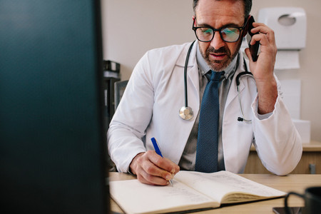 Doctor talking on cell phone and making notes