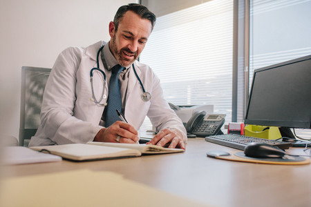 Doctor writing in his diary sitting at clinic desk