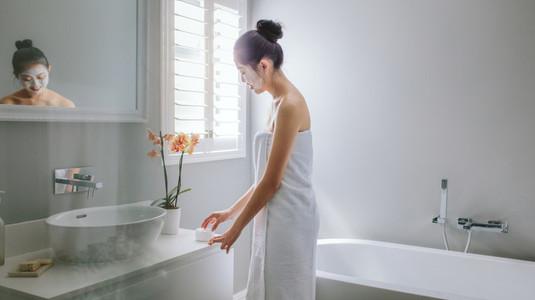 Woman grooming herself in bathroom