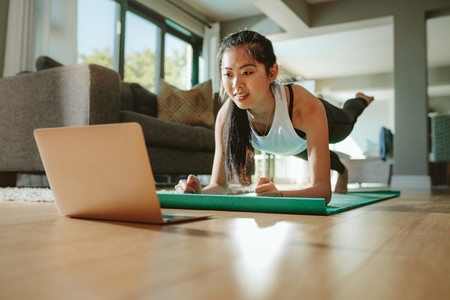 Woman watching sport training online on tablet