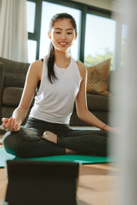 Fit woman watching video on tablet pc and doing yoga