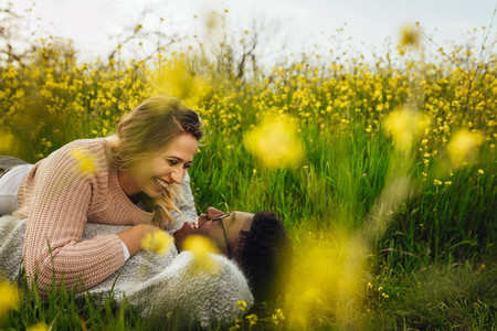 Smiling couple lying on meadow outdoors