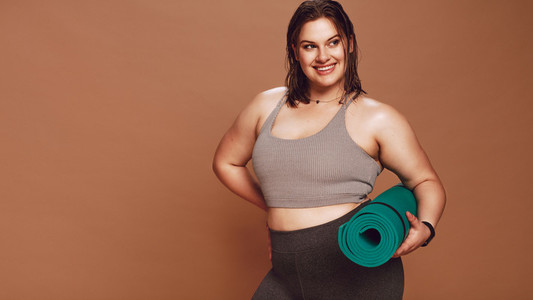 Smiling oversized woman with yoga mat