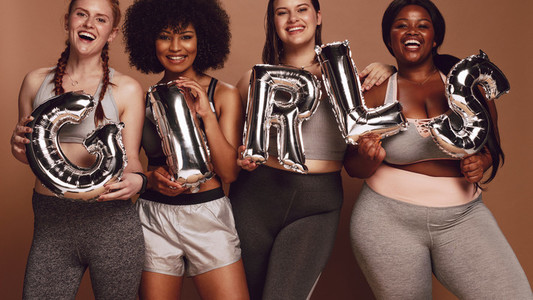 Diverse group of women with girl word in balloon letters