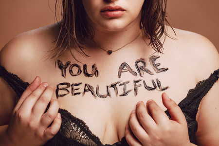 Plus size woman with you are beautiful written on her body