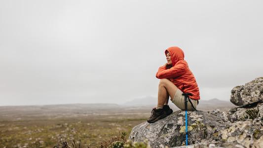 Woman trekker sitting on a hill