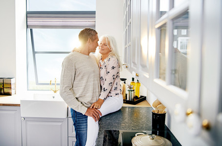 Romantic senior couple sharing a moment in their kitchen