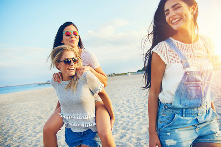 Three happy female friends walking on beach