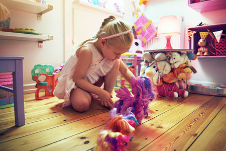 Girl placing toys in line on floor