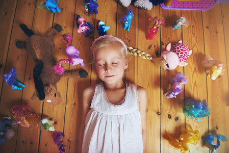 Girl lying on floor with her toys