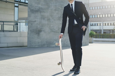 Man wearing suit standing and holding skateboard