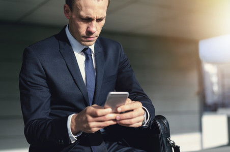 Serious businessman wearing suit using his smartphone