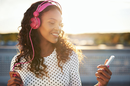Attractive woman listening to music on a rooftop