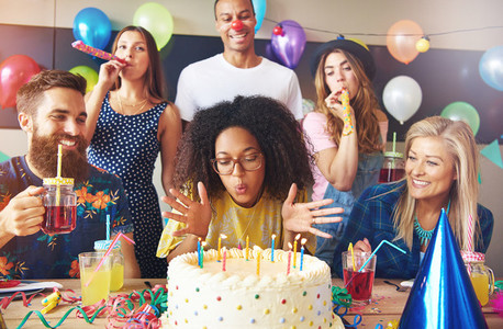 Woman blowing out candles on her cake