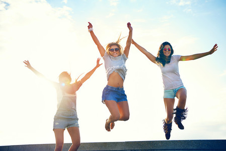 Three joyful young women leaping in the air
