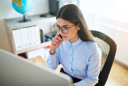 Woman in eyeglasses on phone in small office