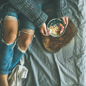 Woman in sweater and jeans eating rice porridge square crop