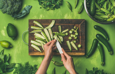 Woman hands cutting green vegetables and greens  top view