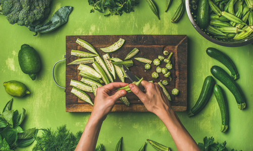 Flat lay of healthy green vegan cooking ingredients over green background
