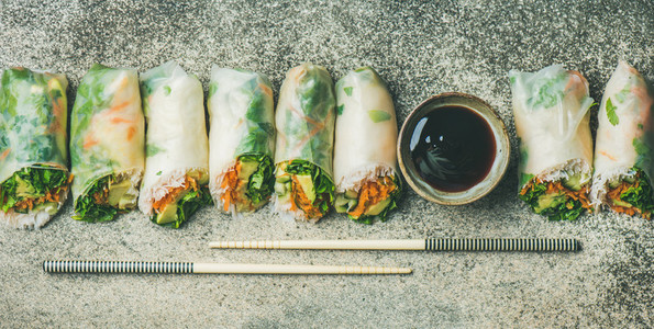 Vegan spring rice paper rolls over concrete background  wide composition