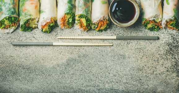 Vegan spring rice paper rolls over concrete background copy space