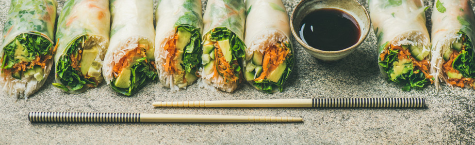 Vegan spring rice paper rolls over concrete background