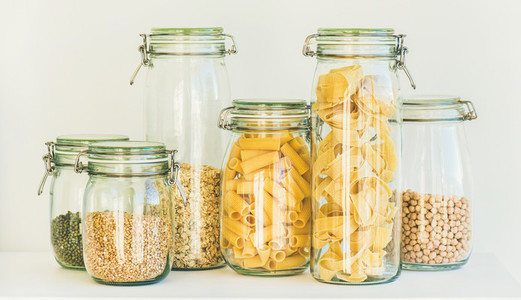 Uncooked cereals grains beans and pasta in jars