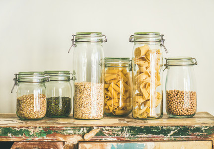 Uncooked cereals  grains  beans and pasta in jars on table