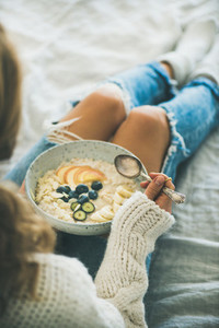 Woman in jeans and sweater eating healthy vegan breakfast